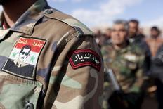 Сирийские дружинники, охраняющие вместе с правительственной армией порядок под Дамаском 5 декабря 2015 года. Около 350 бойцов сирийских проправительственных формирований и мирных жителей из двух осажденных шиитских городов на северо-западе Сирии сели в автобусы и машины скорой помощи, которые отправятся в сторону турецкой границы в рамках соглашения между воюющими сторонами, достигнутого при посредничестве ООН, сообщили сотрудники гуманитарных служб. REUTERS/Omar Sanadiki