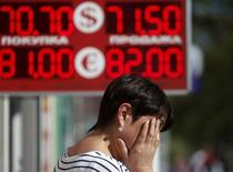 Женщина закрывает лицо руками, стоя у обменника в Москве 24 августа 2015 года. Курс рубля к доллару обновил антирекорды на последней неделе года, обвалившись в понедельник до новой минимальной отметки. REUTERS/Sergei Karpukhin