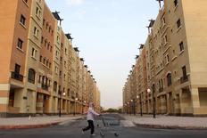 Arabia Saudí, cuyas finanzas públicas se han visto perjudicadas por los bajos precios del petróleo, anunció planes para reducir su déficit presupuestario récord con recortes al gasto, reformas a los subsidios de la energía y un alza en los ingresos obtenidos por impuestos y privatizaciones. En la imagen, un hombre empuja un carro de compra mientras pasa por bloques de viviendas en Riad el 21 de diciembre de 2015. REUTERS/Faisal Al Nasser