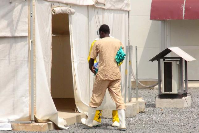 A health worker enters a tent in an Ebola virus treatment center in Conakry, Guinea, November 17, 2015. REUTERS/Saliou Samb