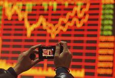 Las bolsas asiáticas entraban en territorio positivo el martes, sacudiéndose de encima caídas anteriores al subir las acciones chinas un día después de anotarse su mayor pérdida en un mes y con los precios del crudo recuperando algo de terreno.  En la imagen, un hombre saca fotos de una pizarra electrónica que muestra información en una casa de valores en Fuyang, provincia de Anhui, el 24 de diciembre de 2015. REUTERS/China Daily