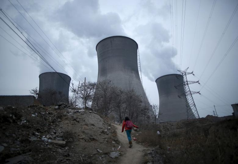 A girl makes her way to her house which locates next to cooling towers of coal-fired power plant in Shijiazhuang, Hebei province, China,  January 28, 2015.    REUTERS/Kim Kyung-Hoon