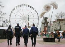 Бельгийские полицейские патрулируют рождественскую ярмарку в центре Брюсселя 27 ноября 2015. Два человека были арестованы в Бельгии в воскресенье и понедельник по подозрению в подготовке нападений в Брюсселе в канун Нового года, сообщила федеральная прокуратура страны. REUTERS/Francois Lenoir