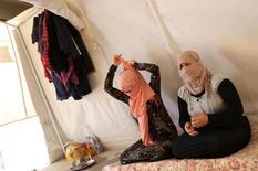 """Сестры-езидки, сбежавшие из плена """"Исламского государства"""", сидят в палатке в лагере беженцев в иракской провинции Духок 3 июля 2015 года. Теологи """"Исламского государства"""" разработали подробные правила, определяющие, при каких условиях """"владельцы"""" порабощенных экстремистской группировкой женщин могут вступать с ними в интимную связь. REUTERS/Ari Jala"""