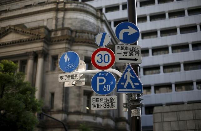 12月30日、日銀によるとマネタリーベース(資金供給量)残高は過去最大の356兆円となり、年間約80兆円増加させるとの金融調節目標を達成した。写真は日銀本店前の交通標識、6月撮影(2015年 ロイター/Toru Hanai)