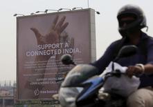 En la imagen, un motorista pasa cerca a un cartel que muestra una iniciativa de Facebook en Bombay, India. 30 de diciembre, 2015. La India se ha convertido en el campo de batalla por el derecho al acceso sin restricciones a Internet, donde empresas de tecnología locales se han unido en contra del fundador de Facebook, Mark Zuckerberg, y su plan de entregar Internet gratuita a la población del país. REUTERS/Danish Siddiqui