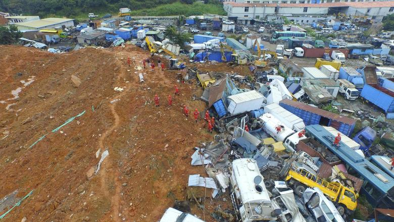 An aerial view shows rescuers walk among damaged vehicles to search for survivors at the site of a landslide which hit an industrial park on Sunday in Shenzhen, Guangdong province, China, December 22, 2015. REUTERS/Stringer