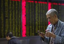 A man checks his mobile phone in front of an electronic board showing stock information at a brokerage house in Beijing, China, January 4, 2016. REUTERS/Kim Kyung-Hoon