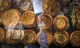 Покупатель протягивает деньги продавцу на рынке в Алма-Ате 23 января 2015 года. Инфляция в Казахстане в 2015 году ускорилась до 13,6 процента с 7,4 процента годом ранее, сообщил комитет по статистике во вторник.  REUTERS/Shamil Zhumatov