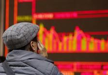 China mantendrá vigente su prohibición a la venta de títulos por parte de los grandes accionistas de las compañías que cotizan en bolsa hasta que el Gobierno publique nuevas normas para tales operaciones, informó el miércoles el diario Shanghai Securities News. En la imagen, un hombre observa un panel electrónico con cotizaciones en una correduría en Pekín, el 6 de enero de 2015. REUTERS/Kim Kyung-Hoon