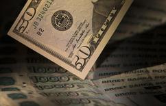 Банкноты российского рубля и доллара США. Москва, 17 февраля 2014 года. Курс доллара поднялся в среду выше отметки в 75 рублей на фоне почти пятипроцентного снижения цен на нефть, российская валюта упала на минимальный уровень с декабря 2014 года. REUTERS/Maxim Shemetov
