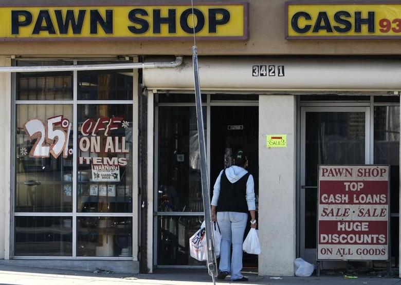 A woman walks into a pawn shop advertising a sale, in Los Angeles January 26, 2009.  REUTERS/Lucy Nicholson
