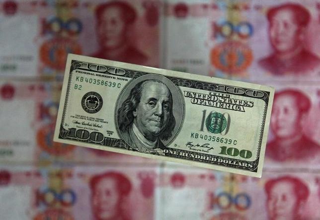 1月7日、中国人民銀行が発表した12月末時点の中国の外貨準備高は3兆3300億ドルで、前月末時点と比べて1079億ドル減少した。減少幅は過去最大。写真はドル紙幣と人民元、北京で2013年5月撮影(2016年 ロイター/Petar Kujundzic)