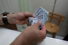 Homem segura notas de dólar. 29 de dezembro de 2015. REUTERS/Esam Omran Al-Fetori
