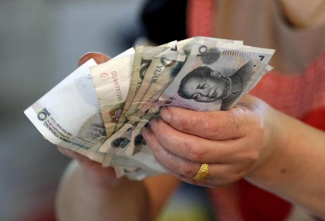 A vendor holds Chinese Yuan notes at a market in Beijing, August 12, 2015. REUTERS/Jason Lee/Files