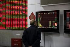 Un inversor mira una pantalla que muestra información bursátil, en una correduría en Shanghái, China, 8 de enero de 2016. Los principales índices bursátiles de China subían más de un 2 por ciento en las primeras operaciones del viernes, después de que Pekín desactivó un mecanismo automático de suspensión de operaciones al que se culpó de exacerbar las caídas del mercado esta semana. REUTERS/Aly Song