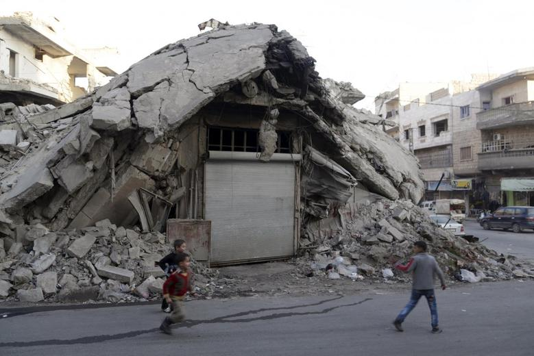 Boys run in front of a damaged building in the rebel-controlled area of Maaret al-Numan town in Idlib province, Syria, December 29, 2015. REUTERS/Khalil Ashawi