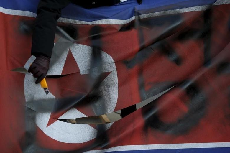 A protester cuts a defaced North Korean flag during an anti-North Korea rally in central Seoul, South Korea, January 7, 2016.  REUTERS/Kim Hong-Ji