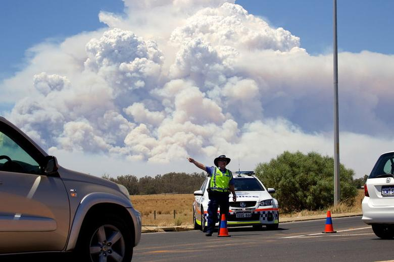 Smoke clouds from a large bush fire are seen behind a police road block at the turn off onto the South Western Highway near Pinjarra, Western Australia, January 7, 2016.    REUTERS/Richard Wainwright/AAP