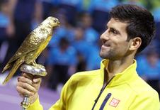 Novak Djokovic of Serbia holds the trophy after winning his Qatar Open men's single tennis final match against Rafael Nadal of Spain in Doha, Qatar, January 9, 2016. REUTERS/Naseem Zeitoon