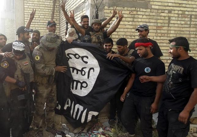 Iraqi security forces stand with an Islamist State flag which they pulled down at the University of Anbar, in Anbar province July 26, 2015. REUTERS/Stringer