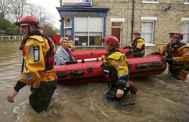 Members of emergency services rescue a woman from a flooded house in York after the river Ouse burst its banks, in northern England, in this December 28, 2015 file photo. REUTERS/Andrew Yates/Files
