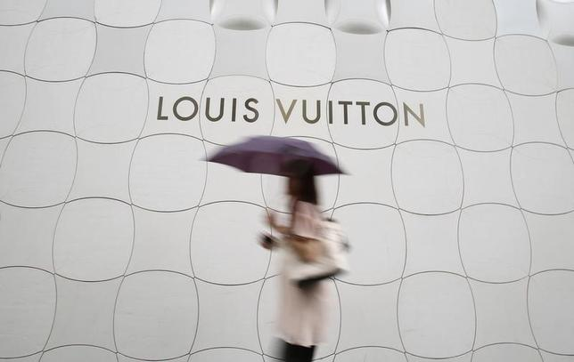 A woman holding umbrella walks past a Louis Vuitton logo outside its branch store at Ginza shopping street in Tokyo August 28, 2014. REUTERS/Yuya Shino
