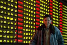 """El yuan, la moneda de China, volvía a dominar los movimientos de los principales mercados cambiarios el lunes, con un alza de un uno por ciento contra el dólar en las transacciones """"offshore"""" después de informaciones que indicaron otra agresiva intervención de parte de Pekín. En la imagen, un inversor pasa junto a una pantalla electrónica con información bursátil en una correduría en  Nanjing, en la provincia china de Jiangsu, el 11 de enero de 2016. REUTERS/China Daily"""