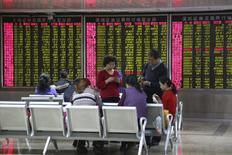 Inversores juegan cartas frente a un tablero electrónico que muestra la información de las acciones, en una correduría en Pekín, China, 4 de enero de 2016. China orientó el yuan al alza el lunes y su cotización en el exterior se apreció frente al dólar, animada por lo que los operadores calificaron como una agresiva intervención de Pekín, aunque los mercados chinos cayeron de nuevo por las persistentes dudas sobre las intenciones de las autoridades financieras. REUTERS/Li Sanxian