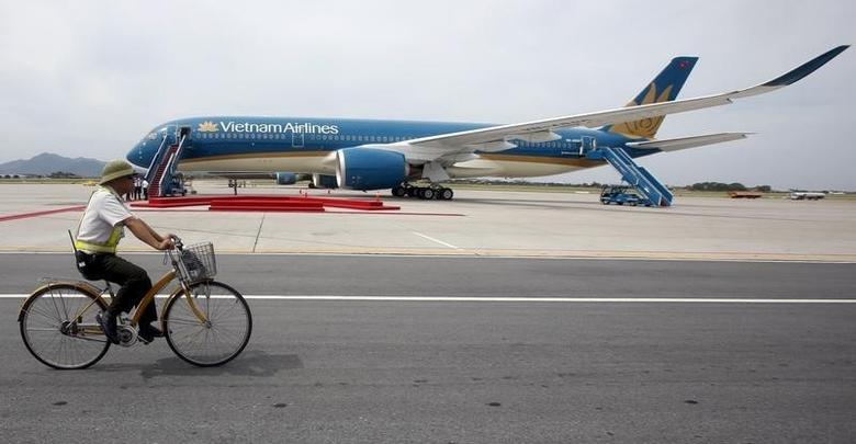 A security guard cycles near an Airbus A350-900 aircraft during its delivery ceremony at Noi Bai International Airport in Hanoi July 2, 2015.   REUTERS/Kham