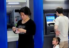 A woman counts yuan banknotes after withdrawing cash from an automatic teller machine (ATM) in Hefei, Anhui province, May 3, 2010. REUTERS/Stringer