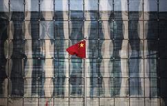 Una bandera de China en la sede de un banco comercial en una calle de un distrito financiero, cerca del Banco Central de China, en Pekín, 24 de noviembre de 2014. La economía de China probablemente creció cerca de un 7 por ciento en el 2015 y sumó 13 millones de nuevos empleos, dijo el martes la principal agencia de planificación económica al anunciar la aprobación de grandes proyectos de infraestructura para evitar los riesgos de una mayor desaceleración. REUTERS/Kim Kyung-Hoon/Files