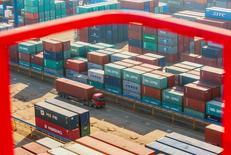 El comercio en China se frenó en diciembre, pero mucho menos de lo esperado, con un dato de exportaciones que superó a muchos de sus rivales regionales después de que el país permitiese al yuan depreciarse con fuerza, lo que desató el temor a una guerra de divisas en las economías de Asia dependientes del comercio. En la imagen de archivo, se ve un camión pasando por delante de contenedores de mercancías en una terminal portuaria en Lianyungang, provincia de Jiangsu, el 23 de enero de 2015. REUTERS/China Daily