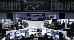 Traders work at their desks in front of the German share price index, DAX board, at the stock exchange in Frankfurt, Germany, January 11, 2016.     REUTERS/Staff/Remote