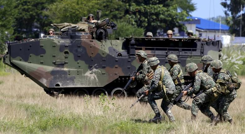 U.S. soldiers aboard an amphibious armoured vehicle watch as Philippine marine troops run during assault exercises in joint drills aimed at enhancing cooperation between the allies at a Philippine Naval base San Antonio, Zambales October 9, 2015.  REUTERS/Erik De Castro