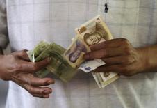 Un cliente cuenta billetes de yuan, en un mercado en Pekín, 12 de agosto de 2015. El banco central chino mantuvo estable al yuan por cuarta sesión seguida el miércoles, calmando los temores acerca de una posible depreciación sostenida de la moneda - al menos por ahora. REUTERS/Jason Lee