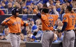 Oct 14, 2015; Kansas City, MO, USA; Houston Astros third baseman Luis Valbuena (18) celebrates with teammates Carlos Gomez (30) and shortstop Carlos Correa (1) after hitting a two-run home run in the 2nd inning against the Kansas City Royals in game five of the ALDS at Kauffman Stadium. John Rieger-USA TODAY Sports