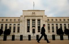 Homem caminha em frente ao Federal Reserve, em Washington. 16 de dezembro de 2015. REUTERS/Kevin Lamarque