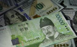 Купюры валюты вона и доллар США в Сеуле 15 декабря 2015 года. Центральный банк Южной Кореи не стал вносить изменения в монетарную политику, дав понять, что некоторое время она останется прежней, однако вместе с тем снизил прогноз экономического роста на 2016 год. REUTERS/Kim Hong-Ji