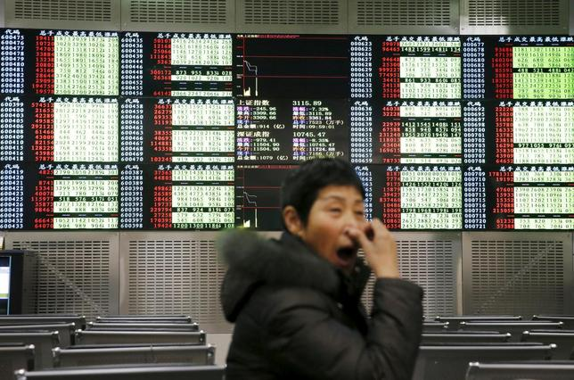 An investor yawns in front of an electronic board showing stock information, after the new circuit breaker mechanism suspended today's stocks trading, in Shanghai, China, January 7, 2016. REUTERS/China Daily