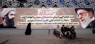 Люди сидят перед транспарантом с изображением верховного лидера Ирана аятоллы Али Хаменеи (справа) в Тегеране 4 января 2016. года. Европейский союз в четверг продлил период приостановки экономических санкций в отношении Ирана на две недели, что стало технической мерой для реализации ядерной сделки между Тегераном и мировыми державами, которая, по словам чиновников, уже не за горами. REUTERS/Raheb Homavandi/TIMA