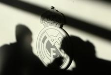 """Тени репортеров падают на логотип """"Реала"""" во время пресс-конференции в Мадриде 9 декабря 2008 года. Международная федерация футбола сообщила в четверг, что запретила мадридским """"Реалу"""" и """"Атлетико"""" регистрировать новых игроков в течение двух трансферных окон за нарушение правил, касающихся трансферов несовершеннолетних футболистов. REUTERS/Andrea Comas"""