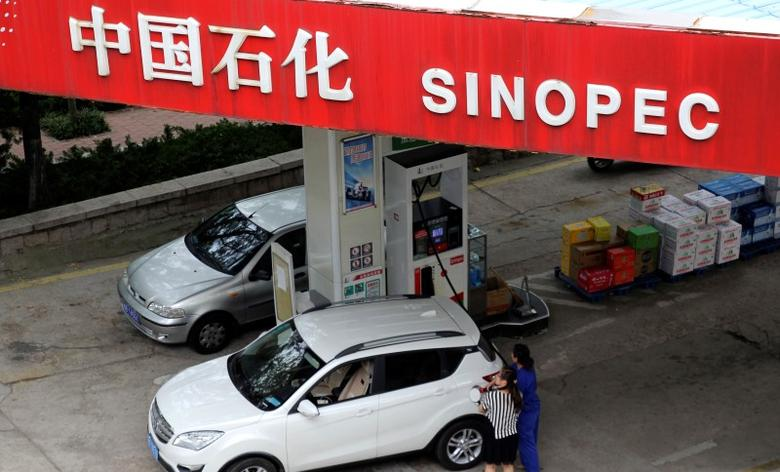 A customer gets the tank of her car filled at a Sinopec gas station in Qingdao, Shandong province September 11, 2014.   REUTERS/Stringer