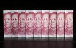 """Ilustración fotográfica que muestra billetes de 100 yuanes chinos, tomada en Pekín. 11 de julio de 2013. China es capaz de mantener el yuan estable en """"un nivel razonable y equilibrado"""", dijo el primer ministro Li Keqiang, según fue citado por la televisión estatal local. REUTERS/Jason Lee/Files"""