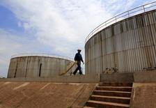 Un empleado de la petrolera Pacific Rubiales camina cerca de unos tanques de depósito de crudo, en Meta, Colombia, 11 de febrero de 2015. La producción promedio de petróleo de Colombia subió un 1,75 por ciento interanual en 2015 y cerró por encima de 1 millón de barriles por día (bpd), por la normalidad en los campos de producción y menos ataques de la guerrilla izquierdista, informó el viernes el Ministerio de Minas y Energía. REUTERS/Jose Miguel Gomez