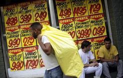 Un hombre pasa por delante de precios de productos en un supermercado en Río de Janeiro. 9 de diciembre 2015. El Banco Central de Brasil elevará las tasas de interés a máximos de casi 10 años la próxima semana para mantener la meta de inflación al alcance, según un sondeo de Reuters, pese a advertencias de que un alza podría empeorar la crisis presupuestaria y profundizar la recesión económica.  REUTERS/Ricardo Moraes