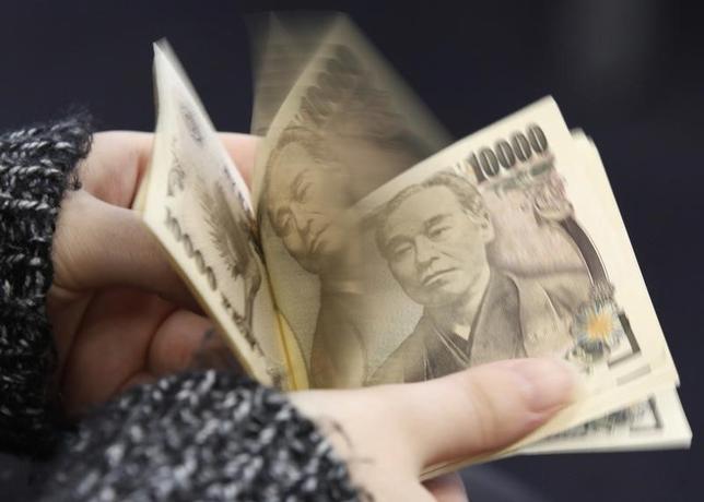 1月15日、終盤のニューヨーク外為市場は、ドルが対円で約5カ月ぶり、対ユーロで2週間半ぶりの安値をつけた。写真は1万円札を数える女性。都内で2013年2月撮影(2016年 ロイター/Shohei Miyano)