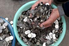 China comenzará a implementar un ratio de reservas exigidas a algunos bancos que participan del mercado del yuan fuera del país, anunció el lunes en un comunicado el Banco Popular de China. En la foro, un hombre sumerge las manos en una colección de monedas de 1 yuan en Zhengzhou, China, el 11 de enero 2016.  REUTERS/Stringer