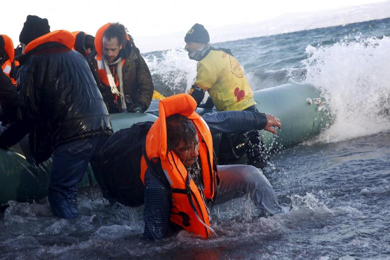 A refugee tries to stand up after falling into the sea as Syrian and Iraqi refugees arrive on a raft on a beach on the Greek island of Lesbos, January 1, 2016. REUTERS/Giorgos Moutafis