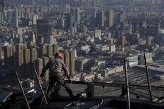 A labourer works atop a construction site of a commercial building as residential complexes are pictured in the background, in Kunming, Yunnan province, China, December 12, 2015. REUTERS/Wong Campion
